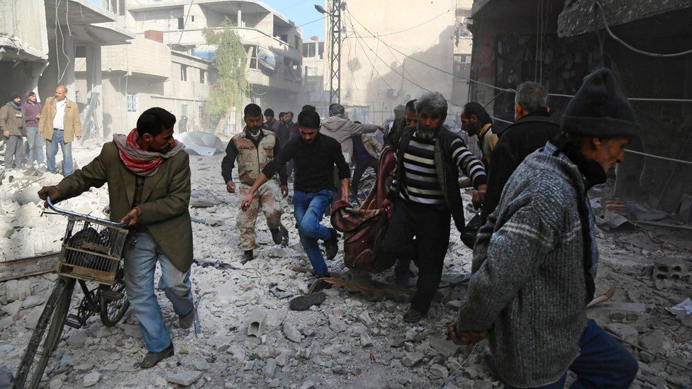 Syrian men carry a body in a blanket after a reported air strike in rebel-controlled Hamouria, in the Eastern Ghouta region outside Damascus (3 December 2017)