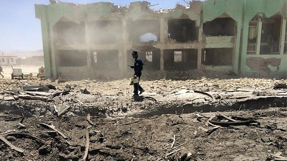 An Afghan policeman inspects the site of a suicide attack in Zabul on 25 May 2015