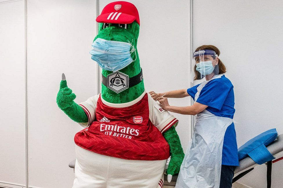 Arsenal mascot Gunnersaurus (left) gets his Covid vaccination from an NHS frontline worker