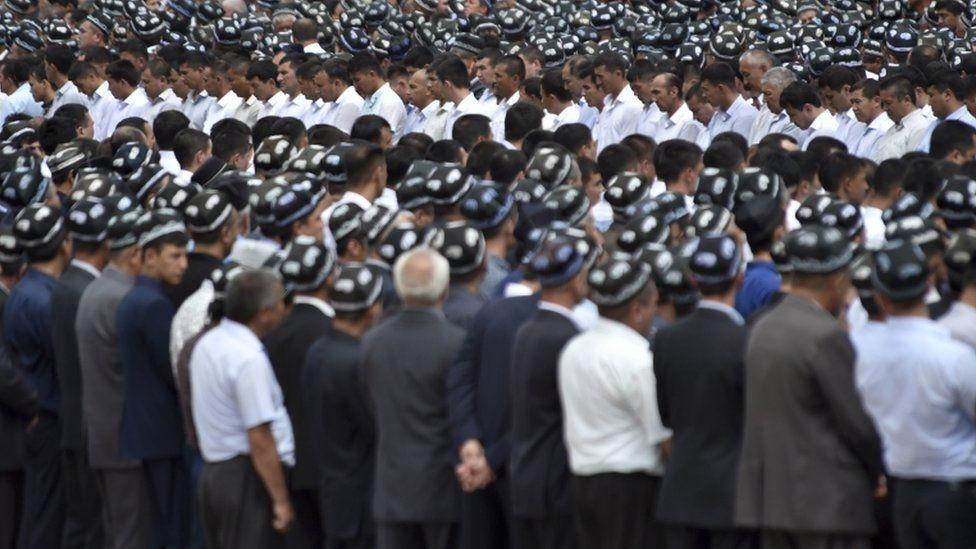 Uzbek men pay respects in Registan square in Samarkand, Uzbekistan