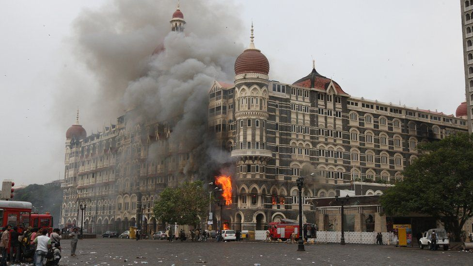 Indian fire brigade officials and bystanders look towards The Taj Mahal hotel in Mumbai on 29 November 2008, as smoke and flames billow out from a section of the building