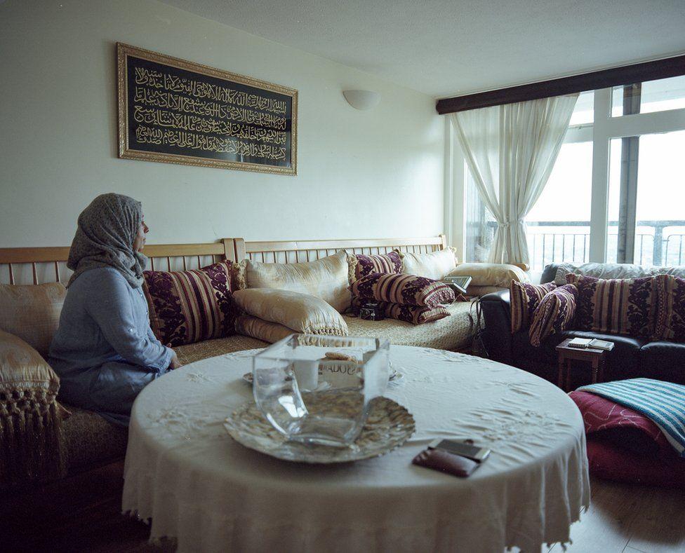 Fatouma sits in her flat