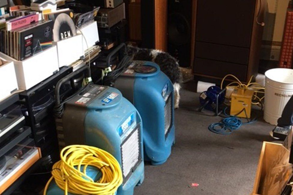 Blow-dryers are being used to dry the flooded carpets