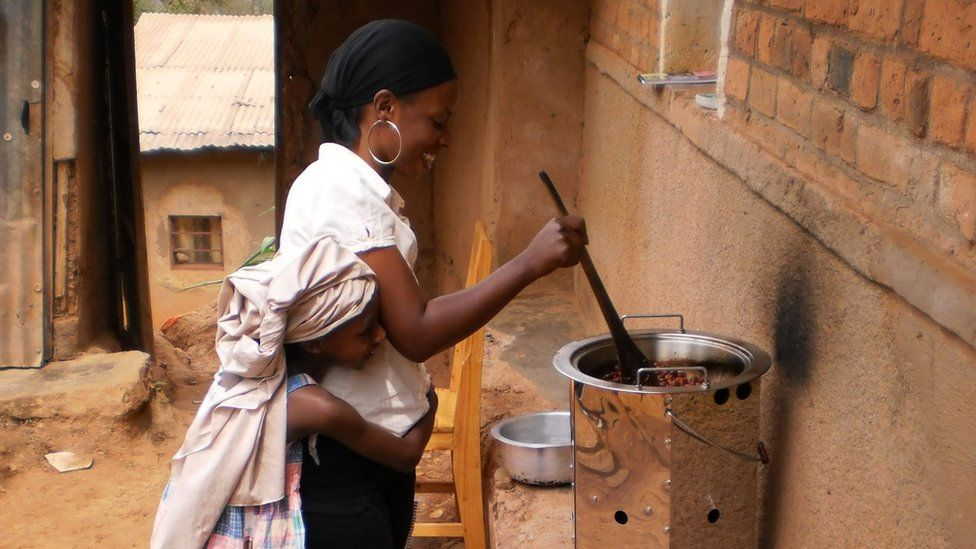 Woman in Rwanda with child cooking on a fuel efficient stove