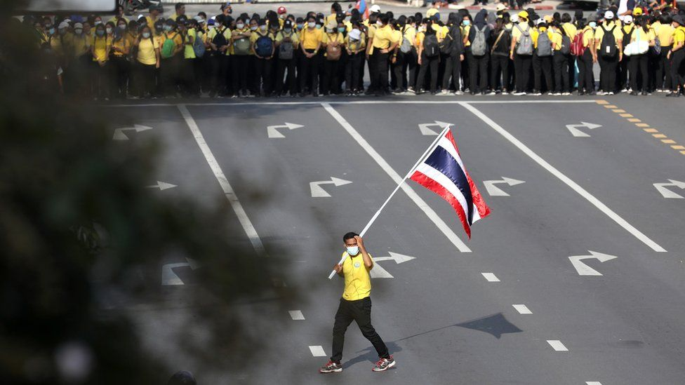 A royalist carries a flag of Thailand as pro-democracy demonstrators stage a Thai anti-government mass protest, on the 47th anniversary of the 1973 student uprising, in Bangkok, Thailand October 14,