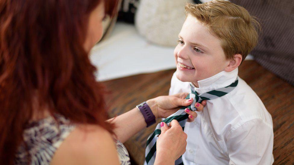 School pupil having his tie tied
