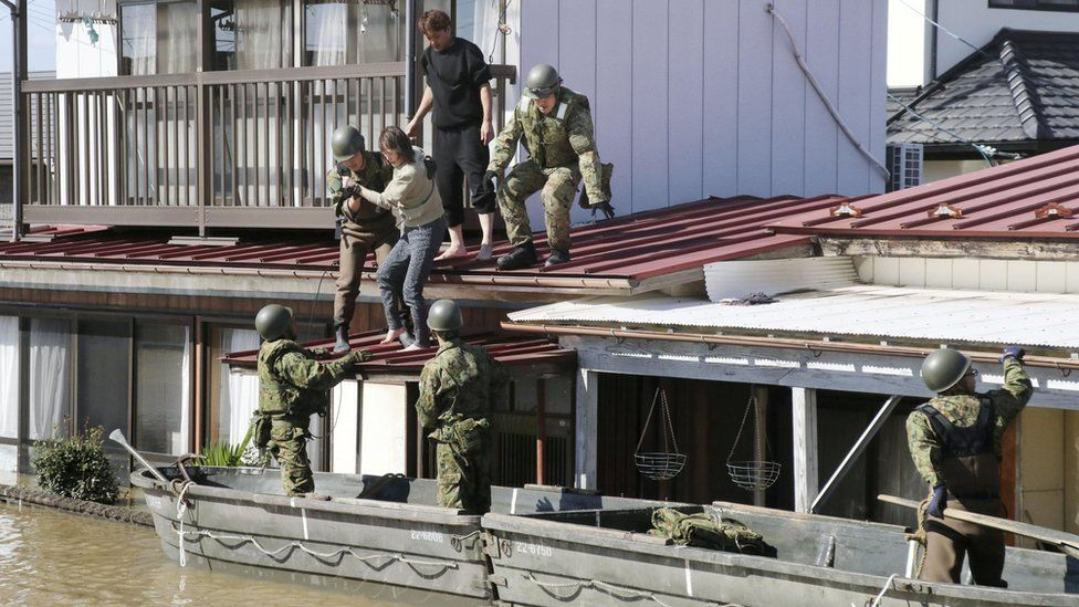 Japanese soldiers use boats to help people in heavy floods
