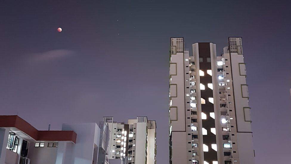 The supermoon is bright red as it appears over a cityscape featuring modern buildings in Singapore.