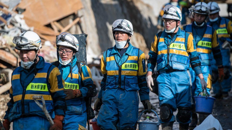 Soldiers and rescue workers check buildings destroyed by a landslide on July 8, 2018 in Kumano near Hiroshima