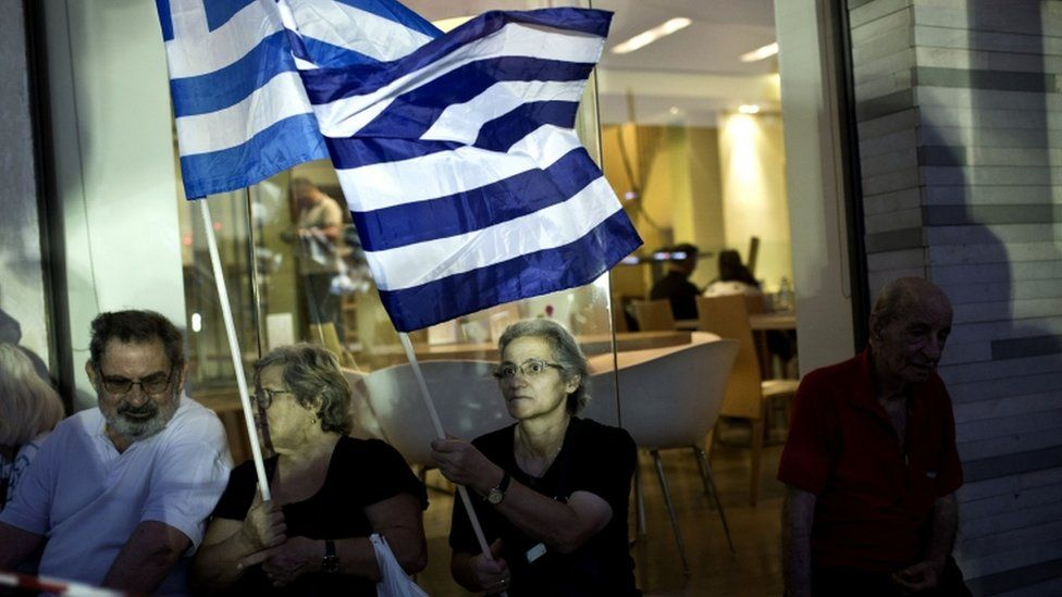 Supporters of the Greek Golden Dawn extreme right party wave the Greek national flag during a pre-election rally in Athens