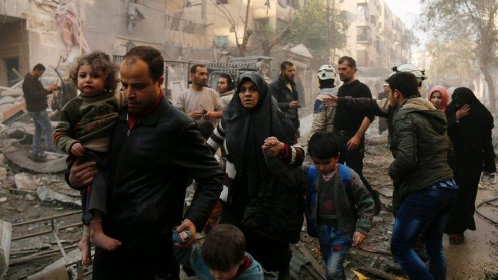Syrians make their way through debris as they leave for a safer place part of Aleppo in this January 2016 file picture