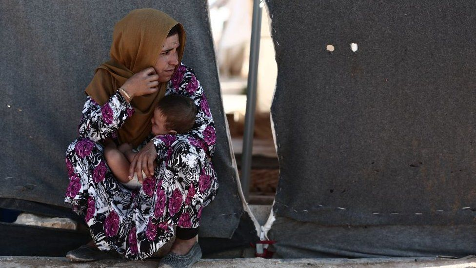 A woman carries a child as she sits in front of a tent at a camp for the displaced from the rebel-held Syrian province of Idlib, at the village of al-Ghadfa