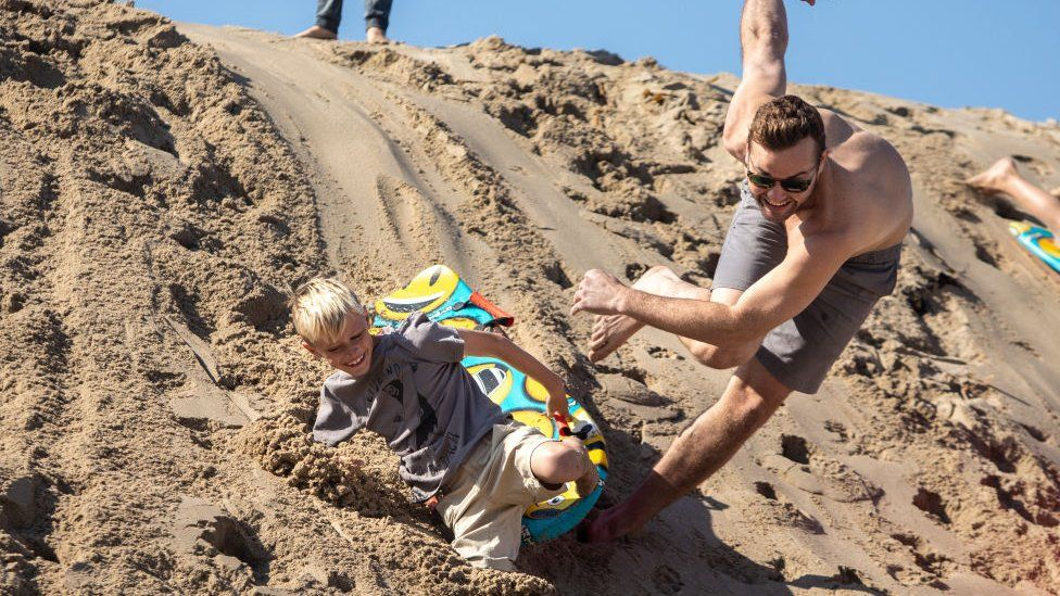 Uncle and nephew sled down a sand dune in Hermosa Beach, California, on 26 November 2020