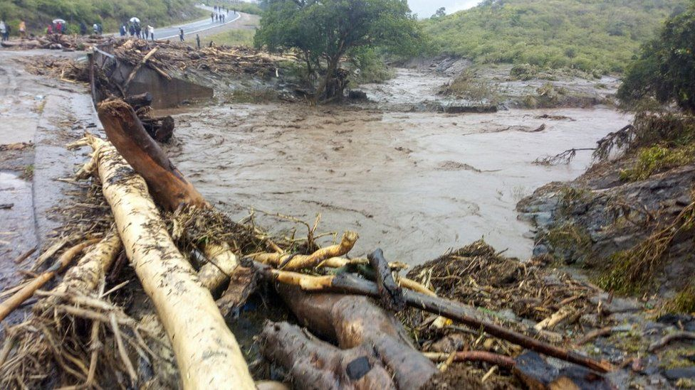 People gather around the road that was destroyed by heavy rain near Kapenguria, West Pokot County