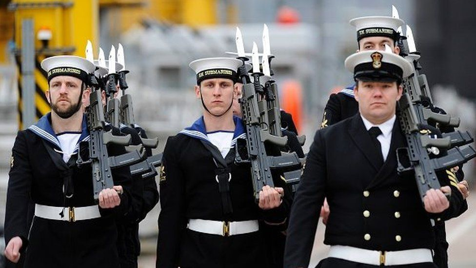 Submariners stand to attention during a ceremony to officially make 'Artful' a commissioned warship of the Royal Navy