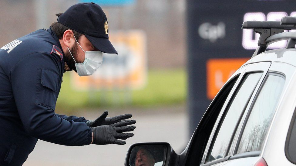 A policeman wearing a face mask warns a driver on the road between Codogno and Casalpusterlengo