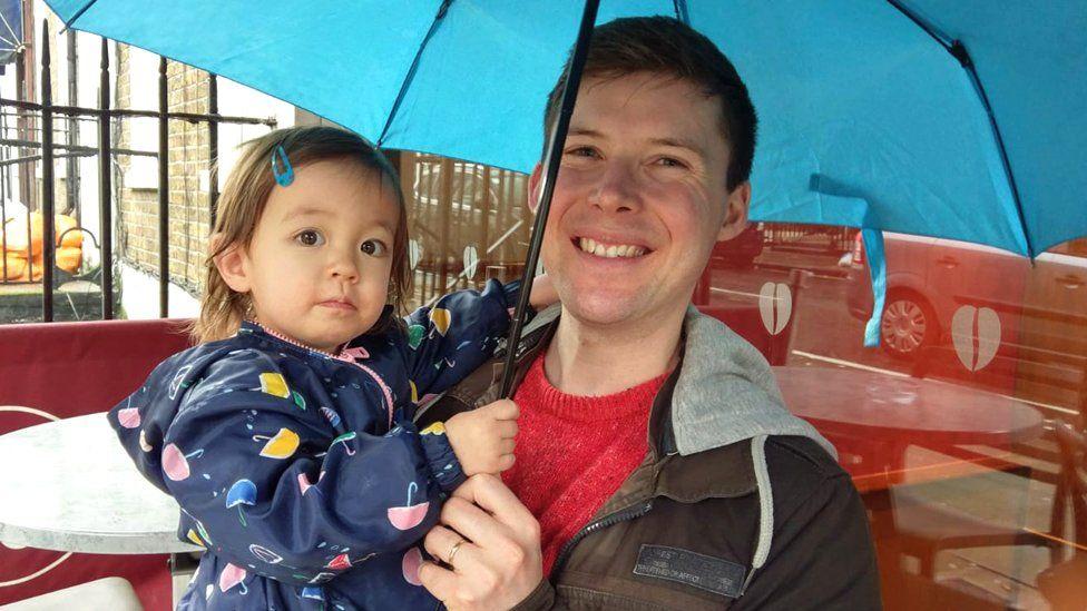 Matthew and his daughter under an umbrella