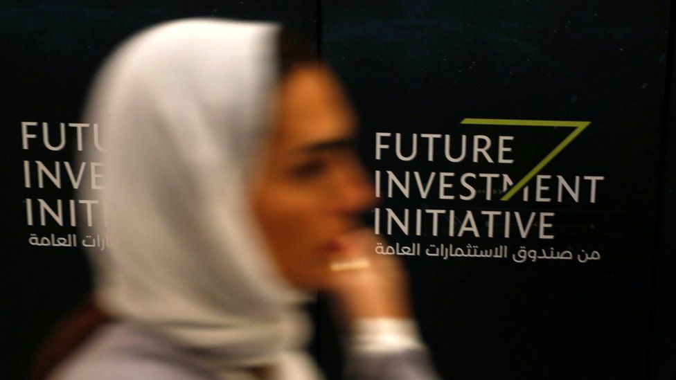 A woman walks past a sign during the Future Investment Initiative conference in Riyadh, Saudi Arabia (24 October 2017)