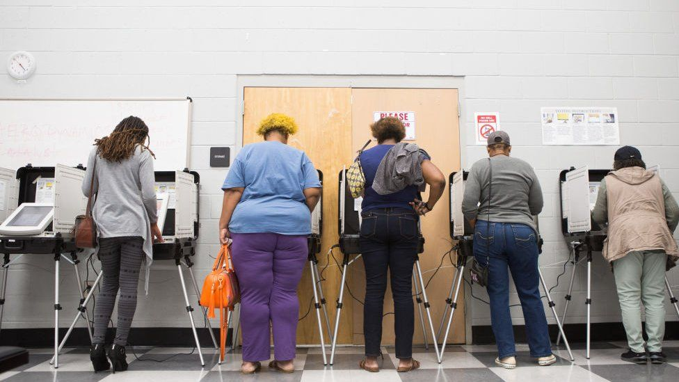 Georgia voters cast a ballot at the polls as part of the state's early voting initiative.