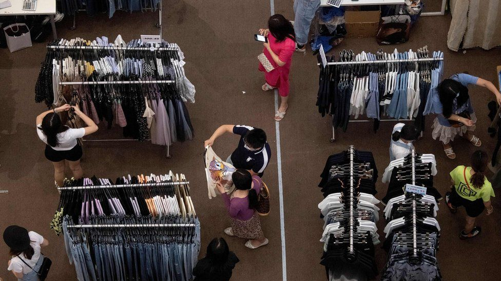 People shop for clothes at a mall in Shenzhen, in China's southern Guangdong province on May 21, 2020.
