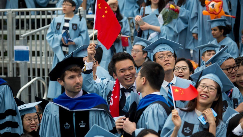 Students wave Chinese flags at Columbia University's commencement ceremony in May 2019.