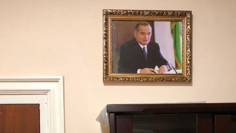 A photo of former Uzbek President Islam Karimov hangs on a off-white wall in a Uzbek hospital
