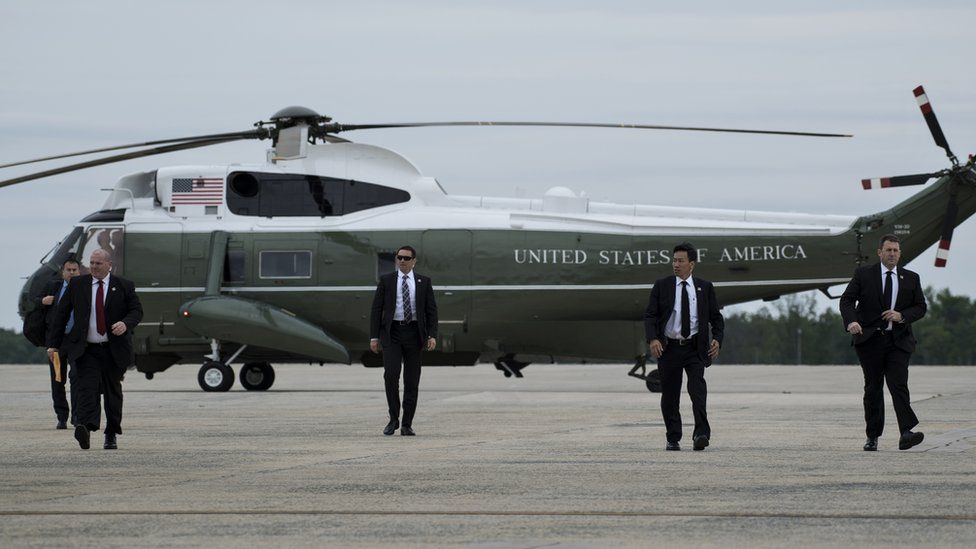 Members of the Secret Service arrive to board Air Force One to escort US President Donald Trump at Andrews Air Force Base in Maryland.