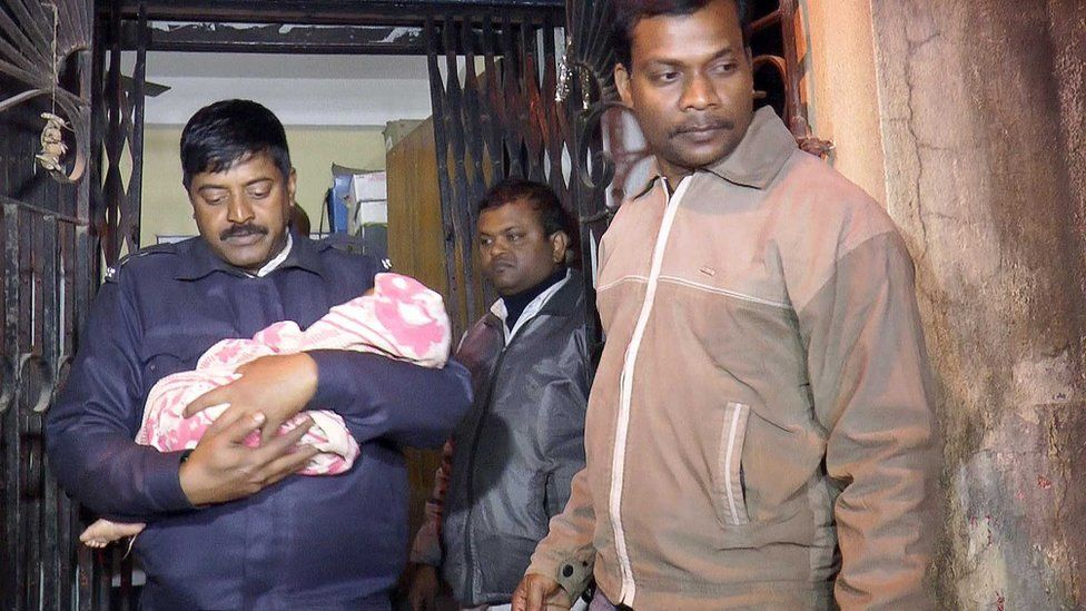 A police officer takes a baby girl from the room in Kolkata