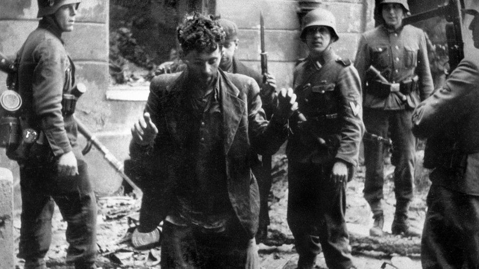 Nazi soldiers arrest a Jew after the Warsaw ghetto uprising in 1943