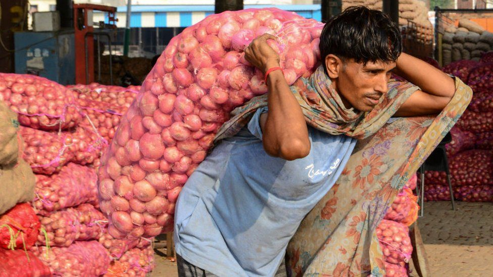 A labourer carries a sack of onions at a wholesale vegetable market on the outskirts of Amritsar on September 19, 2019.