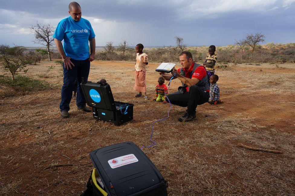 Men setting up mobile network in Sudan