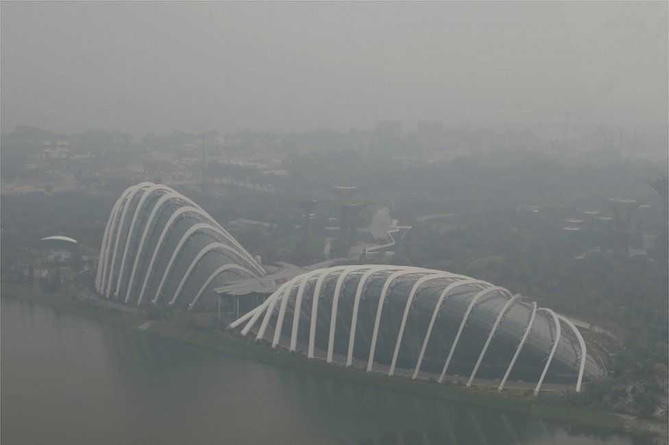 A view of the Flower Dome and Cloud Forest conservatories of Gardens by the Bay and the southern coast of Singapore shrouded by haze in Singapore 10 September 2015