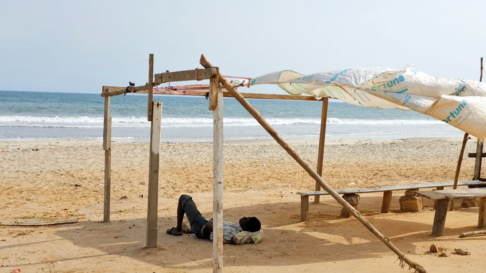A man lying down on a deserted beach in Accra, Ghana - Monday 31 March 2020
