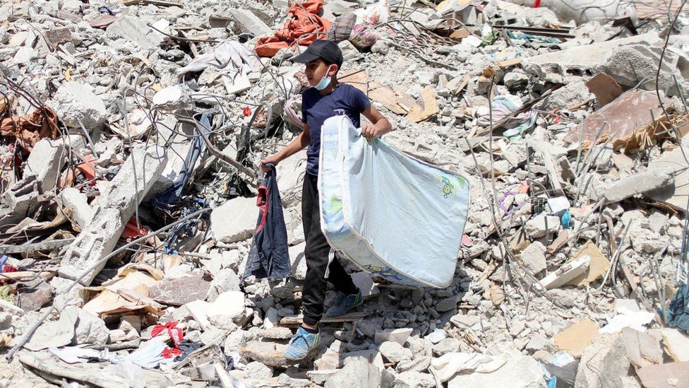 A Palestinian boy carries a mattress as he walks over the rubble of destroyed buildings in Gaza City (2 June 2021)