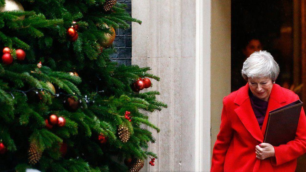 Theresa May walks past the Christmas tree outside 10 Downing Street