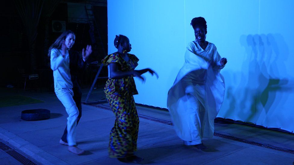 Franco-Swiss dancer Nina Berclaz, Hadiako Sanou (wife of Maboudou) and Latifatou Ouédraogo dance during a rehearsal on the eve of the premiere of the first act of Là-bas ou Ici (Here or There) at the Institut Français in Ouagadougou on April 22, 2021.