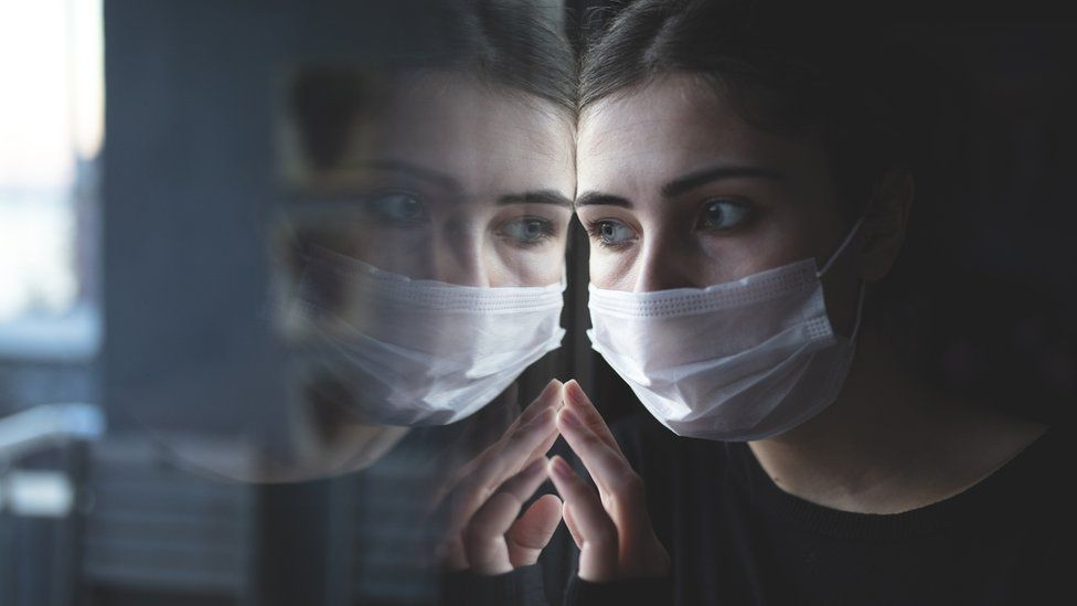 Woman in surgical mask looking out of a window