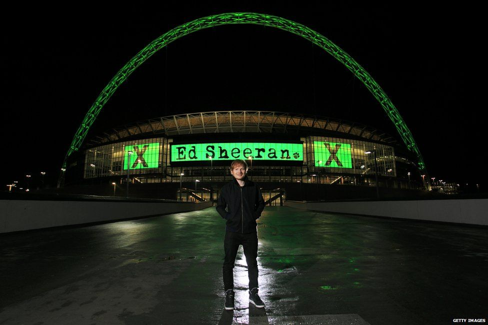 Ed Sheeran standing outside Wembley Stadium