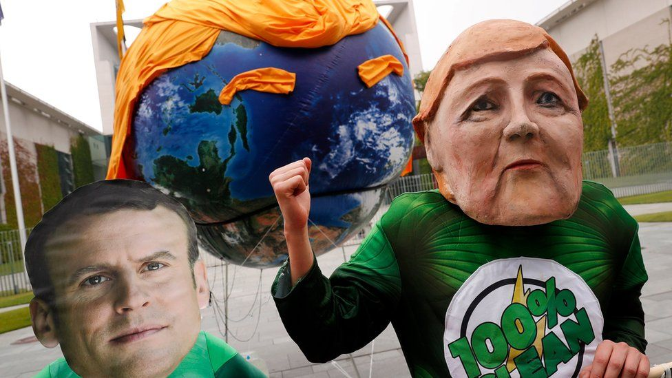Two protestors wearing face masks of German Chancellor Angela Merkel (R) and French President Emmanuel Macron (L) demonstrate outside the German Chancellery ahead of the arrival of the European leaders in Berlin, Germany, 29 June 2017