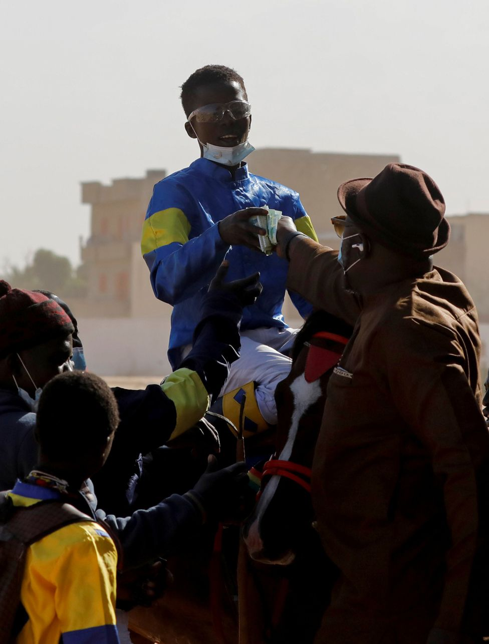 Fallou Diop is handed prize money after winning a race in Thies, Senegal, 7 February 2021