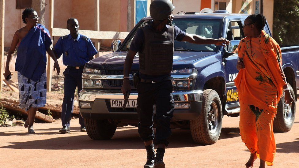 Malian security forces evacuate two women from an area surrounding the Radisson Blu hotel in Bamako