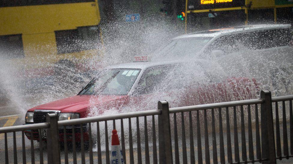 A cab drives through heavy rain in Hong Kong