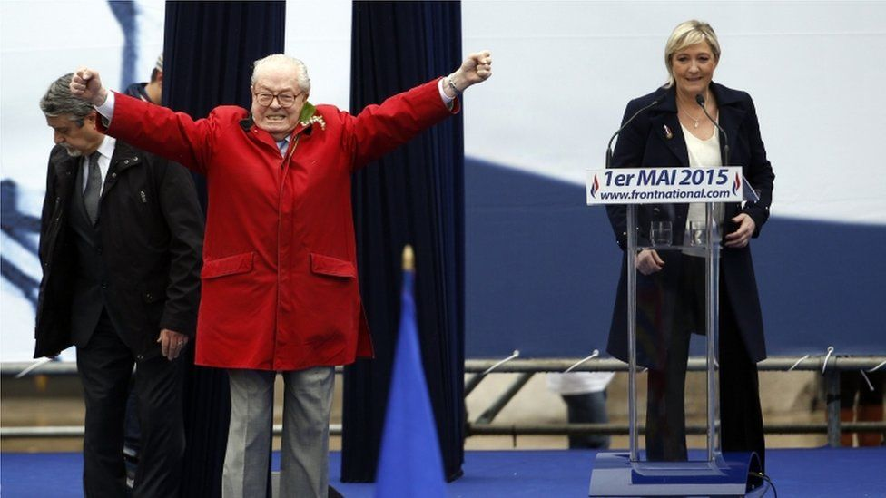 Jean-Marie Le Pen gestures on stage alongside Marine Le Pen