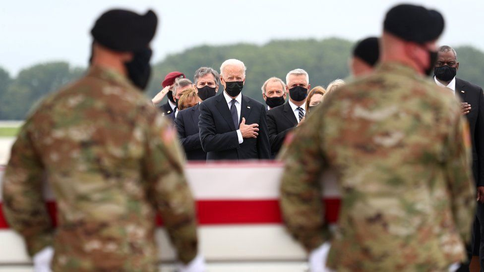 US President Joe Biden salutes during the dignified transfer of the remains of US Military service members who were killed by a suicide bombing at the Hamid Karzai International Airport, at Dover Air Force Base in Dover, Delaware