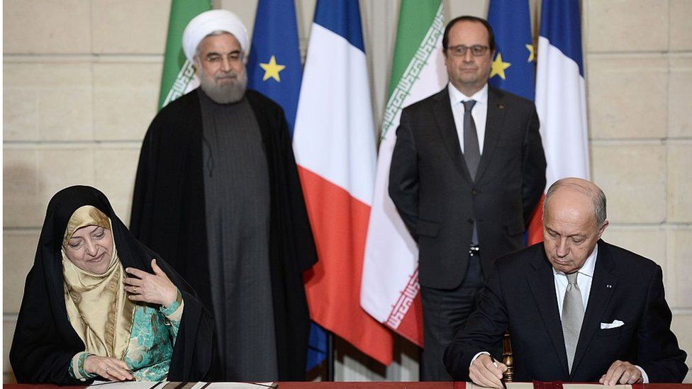 French Foreign Minister Laurent Fabius (right), Iranian vice-president and head of the Environmental Protection Organisation Masoumeh Ebtekar (left), Iranian President Hassan Rouhani (back left) and French President Francois Hollande (Jan 2016)