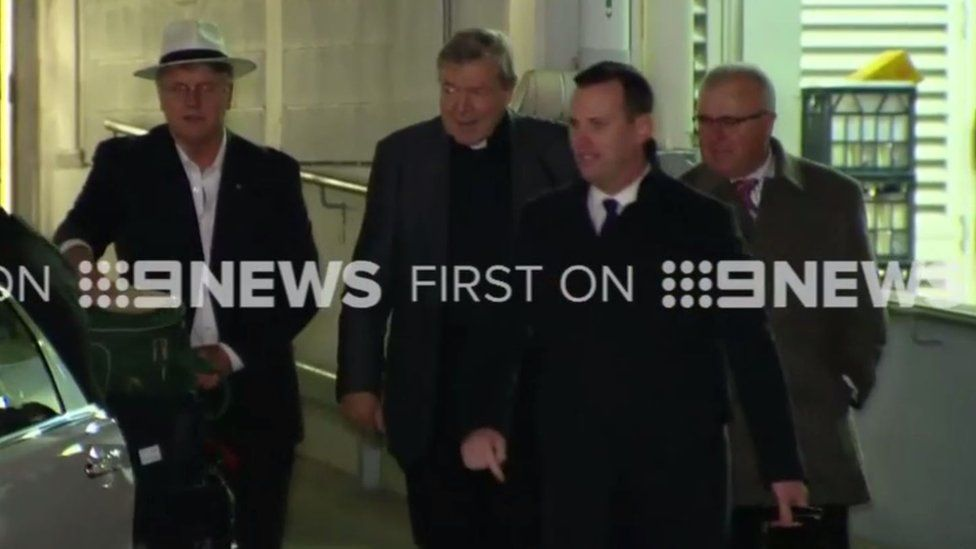 Cardinal Pell (second from left) arrives in Sydney, accompanied by police and private security staff