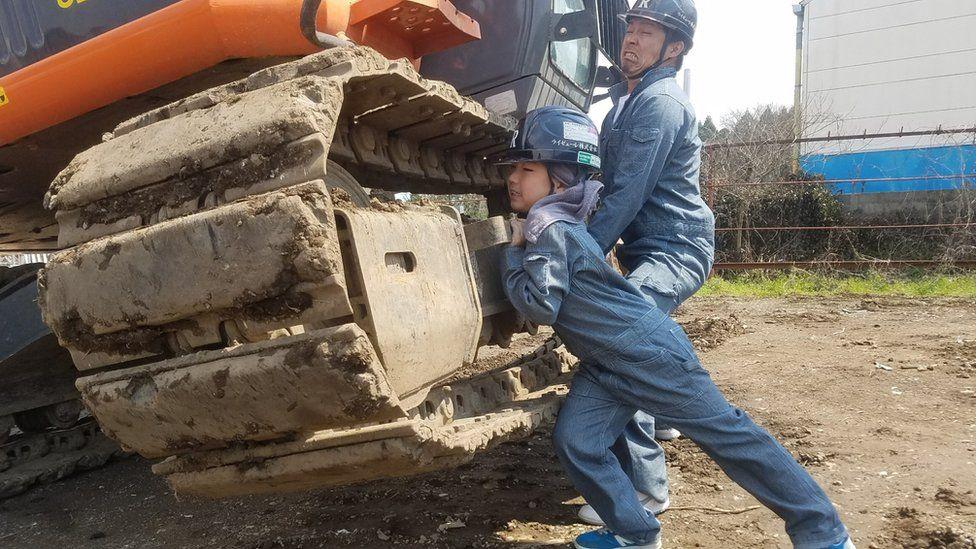 Masato Nakajima and daughter pretend to lift a digger