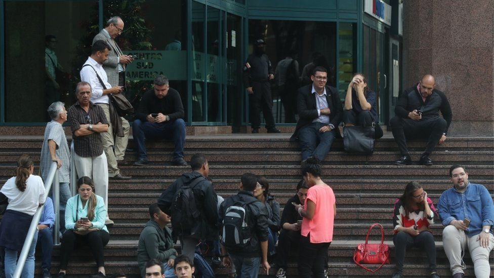 People wait outside of the building with the office of Venezuela's Opposition leader Juan Guaido, in Caracas. 21 Jan 2010