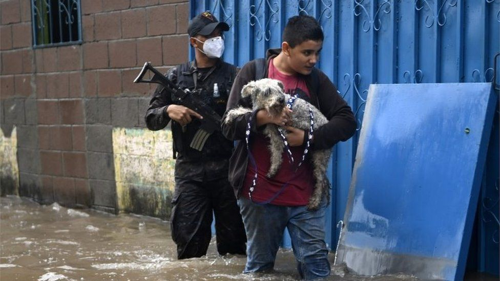 A boy carries his dog as he wades through the water in the flooded Santa Lucia colony in Ilopango, El Salvador, during Tropical Storm Amanda, on May 31, 2020.
