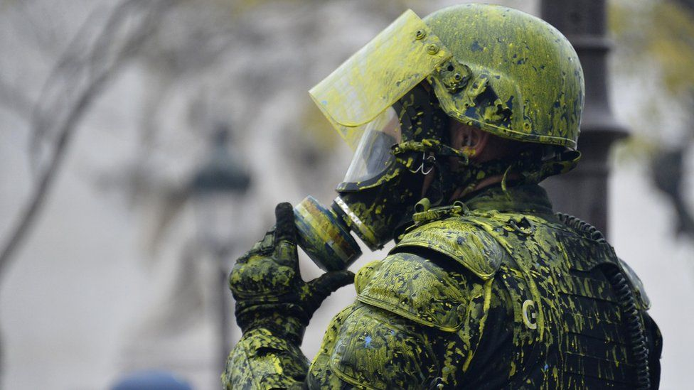 A Riot police officer covered with yellow paint pictured near Arc de Triomphe area